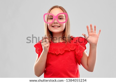 party props, photo booth and childhood concept - smiling girl in red shirt with big paper glasses waving hand over grey background