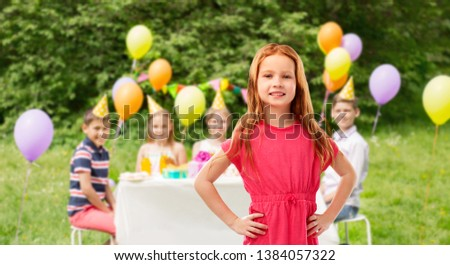 childhood and people concept - smiling red haired girl posing in pink dress over birthday party at summer park background #1384057322