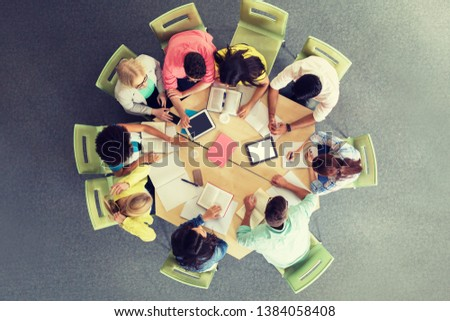 education, high school, people and technology concept - group of international students sitting at table with tablet pc computers, books and notebooks at university library from top #1384058408