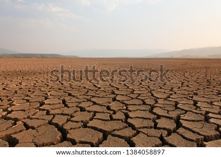 Dry river and lake after drought impact on summer, Landscape of Cracked earth metaphor climate change and global warming #1384058897