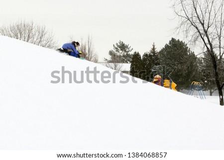 Idaho Falls, Idaho, USA  Feb 18, 2017 A mother and son rid down a snowy hillside on a snow sled. #1384068857