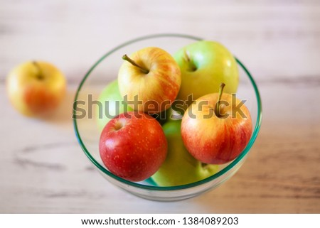 Few ripe appples in transparante plate and one apple on the table in kitchen.  Organic fruits. Light from window. #1384089203