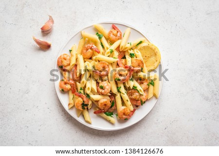 Penne Pasta with Prawns or Shrimps, lemon and garlic on white, top view, copy space. Lemon pasta with sauteed shrimps, fresh seafood. #1384126676