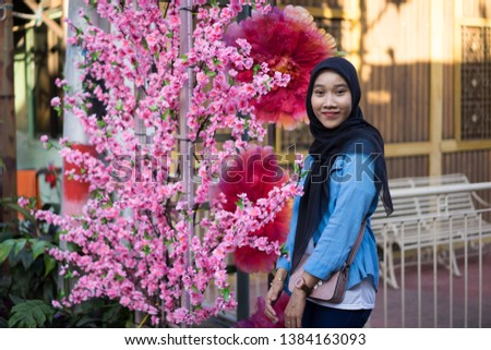 asian hijab girl with pink flower #1384163093