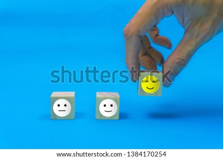 Conceptual the customer responded to the survey. The client using hand choose happy face smile icon on wood block. Depicts that customer is very satisfied. Service experience and satisfaction concept. #1384170254