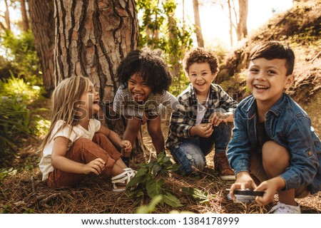 Group of cute kids sitting together in forest and looking at camera. Cute children playing in woods. #1384178999