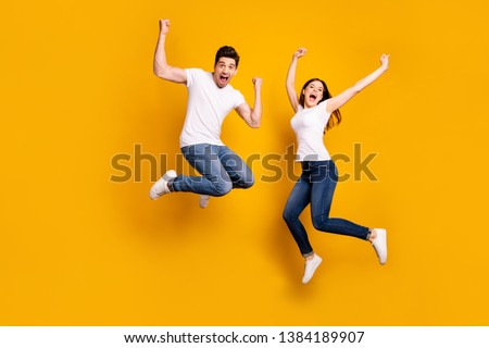 Full length body size photo funky she her he him his pair jumping high raised fists yell scream shout loud cheerleader football fans wear casual jeans denim white t-shirts isolated yellow background Royalty-Free Stock Photo #1384189907
