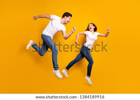 Full length side profile body size photo funky she her he him his pair jumping high hurry shopping raised fists yell scream shout loud wear casual jeans denim white t-shirts isolated yellow background #1384189916