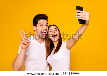 Portrait of his he her she two nice attractive lovely stylish trendy cheerful positive people making taking selfie enjoying showing v-sign isolated over vivid shine bright yellow background #1384189994