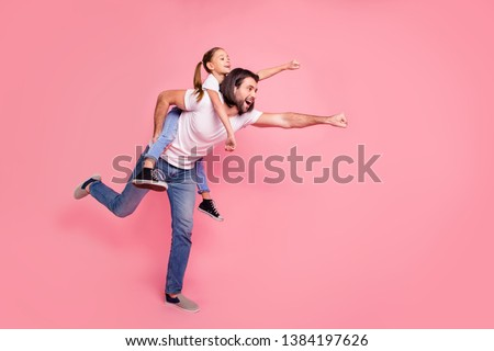 Full length side profile body size photo she her little lady he him his daddy dad hold little princess piggyback hands arms ready fly wear casual white t-shirts denim jeans isolated pink background #1384197626