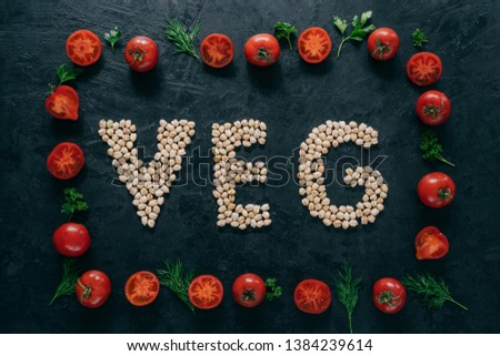 Vegetable frame made of tomatoes and green parsley, dill. Letter shaped garbanzo in middle. Raw vegetarian products. Healthy eating concept #1384239614