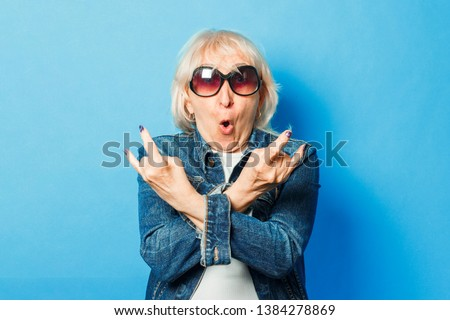 An old lady in a denim jacket, sunglasses makes a gesture on the rock on a blue background. Concept fashionable grandmother, old woman, action rockers Goat. Royalty-Free Stock Photo #1384278869