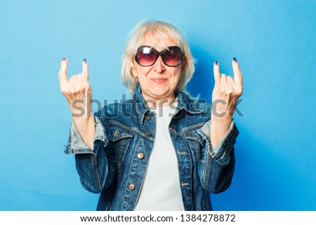 An old lady in a denim jacket, sunglasses makes a gesture on the rock on a blue background. Concept fashionable grandmother, old woman, action rockers Goat. Royalty-Free Stock Photo #1384278872