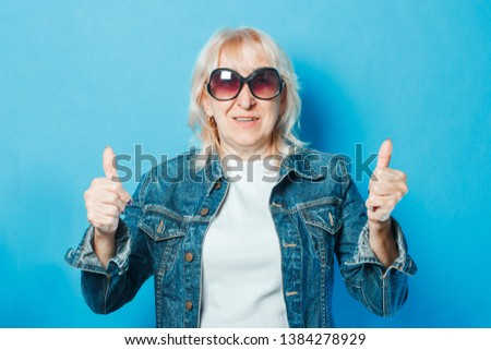 An old lady in a denim jacket and sunglasses is showing a gesture with her hands. Thumb up on a blue background. Concept fashionable grandma, old woman, funky action. #1384278929