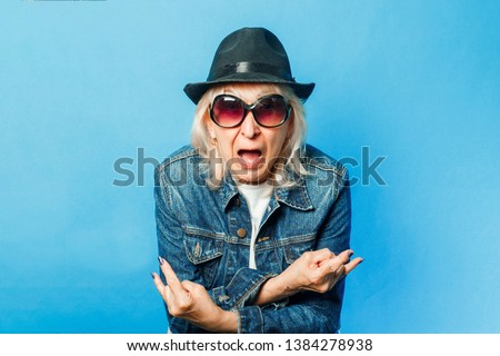 An old lady in a denim jacket, sunglasses and a hat makes a gesture on the rock on a blue background. Concept fashionable grandmother, old woman, action rockers Goat. Royalty-Free Stock Photo #1384278938