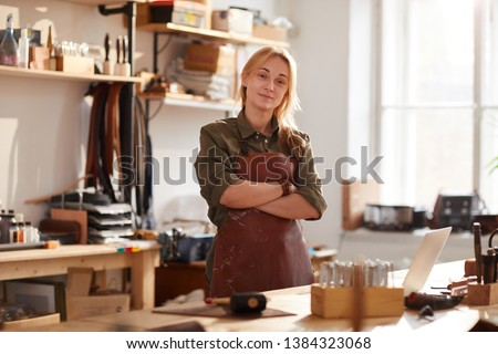 Warm toned portrait of confident female artisan standing with arms crossed while posing in workshop #1384323068