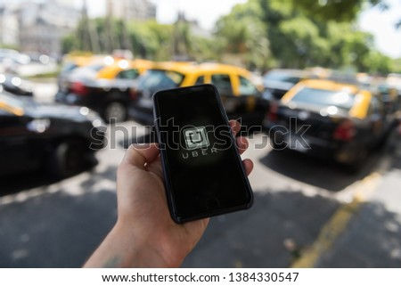 Capital Federal, Buenos Aires, Argentina: 2 20 2018; A smartphone with the Uber application is seen in the middle of taxis #1384330547