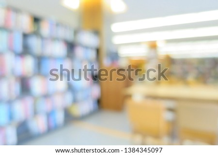 Blurred of the interior of the public library with wooden tables, chairs and books in bookshelves. Education and book's day background concept. #1384345097