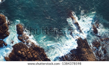 Waves breaking against a rocky patch in the ocean #1384378598