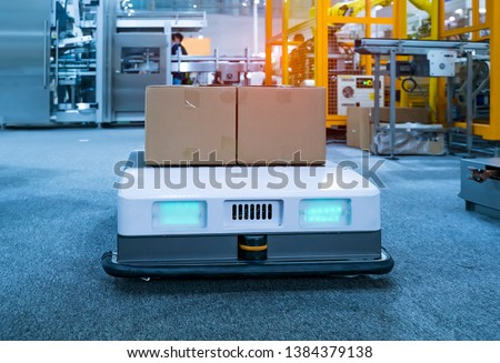 warehouse robot car carries cardboard box assembly in factory Royalty-Free Stock Photo #1384379138