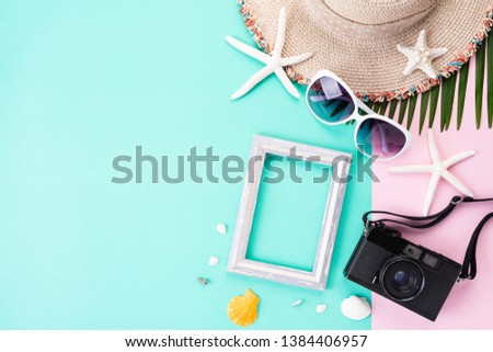 Beach accessories retro film camera Picture Frame, sunglasses, flip flop, starfish beach hat and sea shell on bright pastel green background for summer holiday and vacation concept.