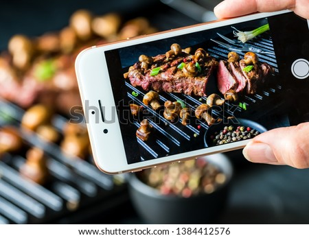 Close up view of a cell phone taking a picture of a strip loin steak on a grill with mushrooms and green peppers against a blurred background of the actual scene.