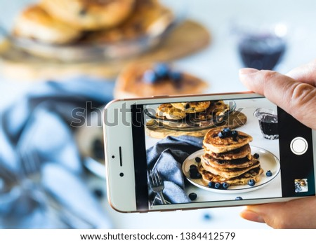 Close up view of a cell phone taking a picture of a stack of blueberry pancakes against a blurred background of the actual scene.