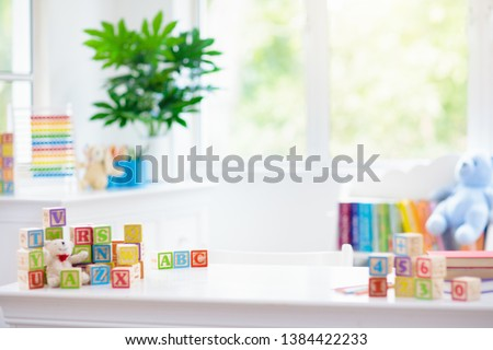 Child learning letters and numbers. Kid with colorful wooden abc blocks. Little boy spelling words with educational block toys. Kids doing school homework at white desk. Bedroom for preschool children #1384422233
