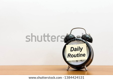 Post it word daily routine alarm clock on wood desk white background.  Sticker notepad paper message daily routine and watch on wooden table for copy space.  #1384424531