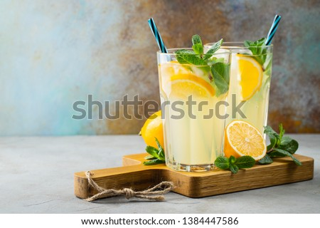 Two glass with lemonade or mojito cocktail with lemon and mint, cold refreshing drink or beverage with ice on rustic blue background. Copy space #1384447586