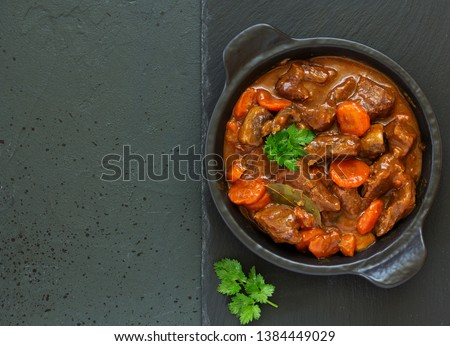 Beef stew in Burgundy. With carrots, onions, peas and champignons in wine. View from above. #1384449029