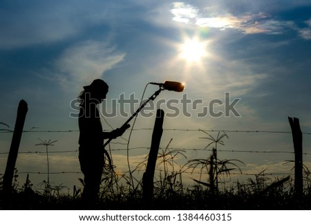 Soundman worker with headphone holding a boom microphone recordi