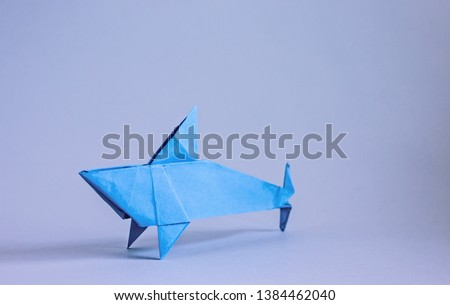 Origami shark fish. Blue paper shark on a blue background. Creativity origami. Origami #1384462040