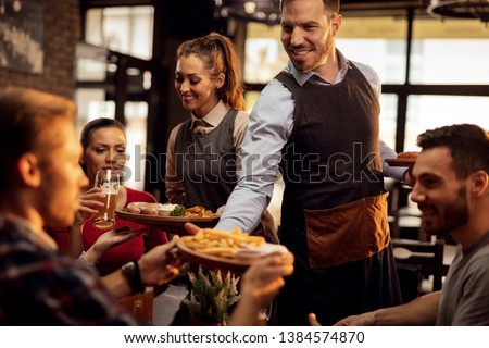 Happy waiters bringing food at the table and serving group of friends in a restaurant. #1384574870