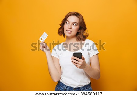 Cheerful young girl wearing t-shirt standing isolated over yellow background, using mobile phone, showing plastic credit card #1384580117