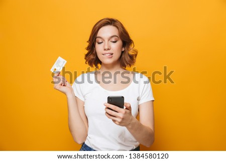 Cheerful young girl wearing t-shirt standing isolated over yellow background, using mobile phone, showing plastic credit card #1384580120