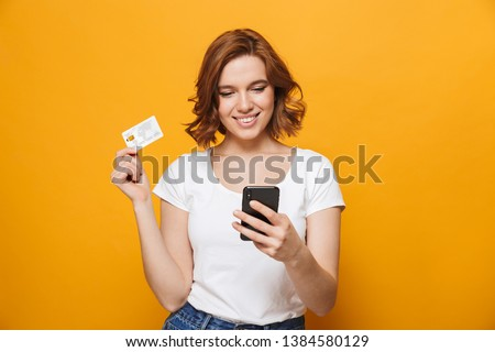 Cheerful young girl wearing t-shirt standing isolated over yellow background, using mobile phone, showing plastic credit card #1384580129