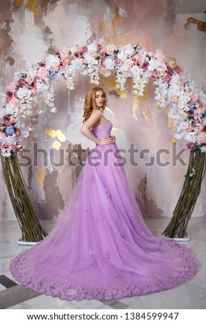 The beautiful girl the blonde in a smart long lilac dress with a train costs near the decorative arch from flowers. #1384599947