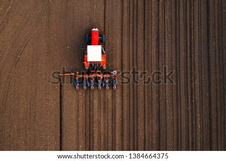 Aerial view of tractor with mounted seeder performing direct seeding of crops on plowed agricultural field. Farmer is using farming machinery for planting process, top view #1384664375
