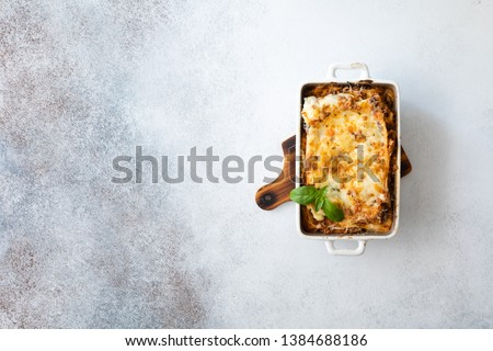 Tasty lasagne with meat, cheese on wooden plate, top view. Traditional italian lasagna with vegetables, basil, minced beef meat, tomato and cheese on concrete background. #1384688186