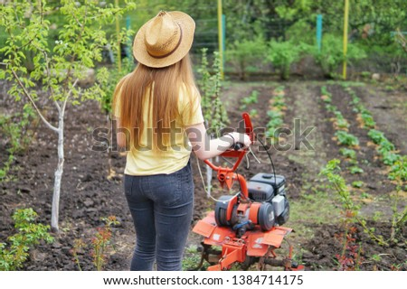A young girl farmer in a yellow T-shirt stands in front of a small garden with a motor-cultivator and prepares to plow a vegetable garden. #1384714175