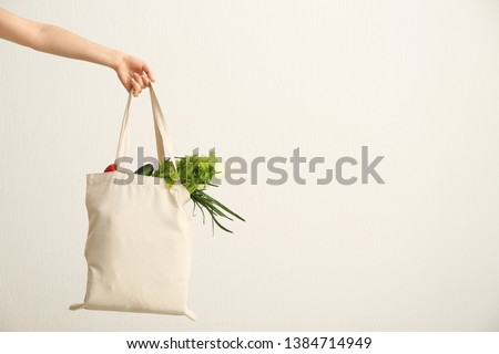 Female hand with eco bag on white background. Zero waste concept #1384714949