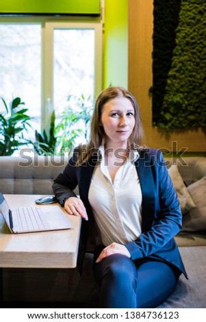 Young business woman working with laptop on the table in the city cafe interior #1384736123