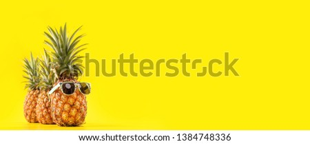 Creative pineapple looking up with sunglasses and shell isolated on yellow background, summer vacation beach idea design pattern, copy space close up #1384748336
