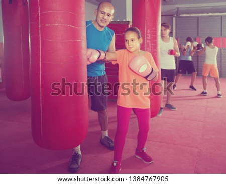 Girl teenager at boxing workout on punching bag with instructor #1384767905