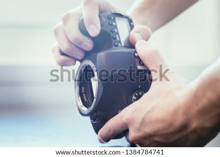 Hands of a photographer are touching a professional reflex camera, open sensor #1384784741