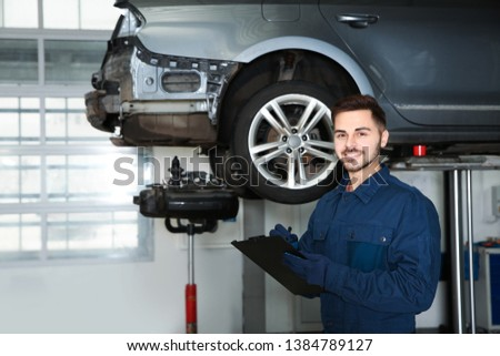 Technician checking car on hydraulic lift at automobile repair shop #1384789127