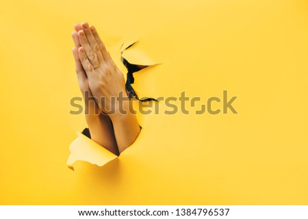 Women's hands folded in a gesture of prayer. A torn hole in yellow paper and the concept of man's conversion to God. Copy space. #1384796537