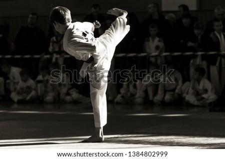 "Taekwondo martial art. A young man in kimano demonstrates a kick. The inscription on the jacket ""Taekwondo"" #1384802999"