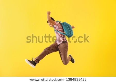 Portrait of jumping African-American teenage boy on color background Royalty-Free Stock Photo #1384838423